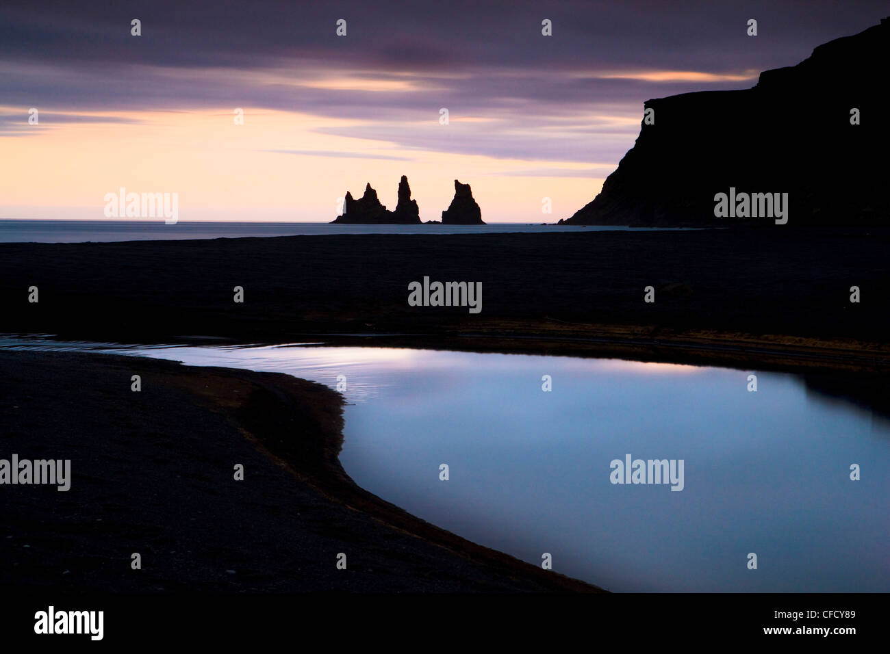 Twilight view towards rock stacks at Reynisdrangar off the coast at Vik, South Iceland, Iceland, Polar Regions - Stock Image