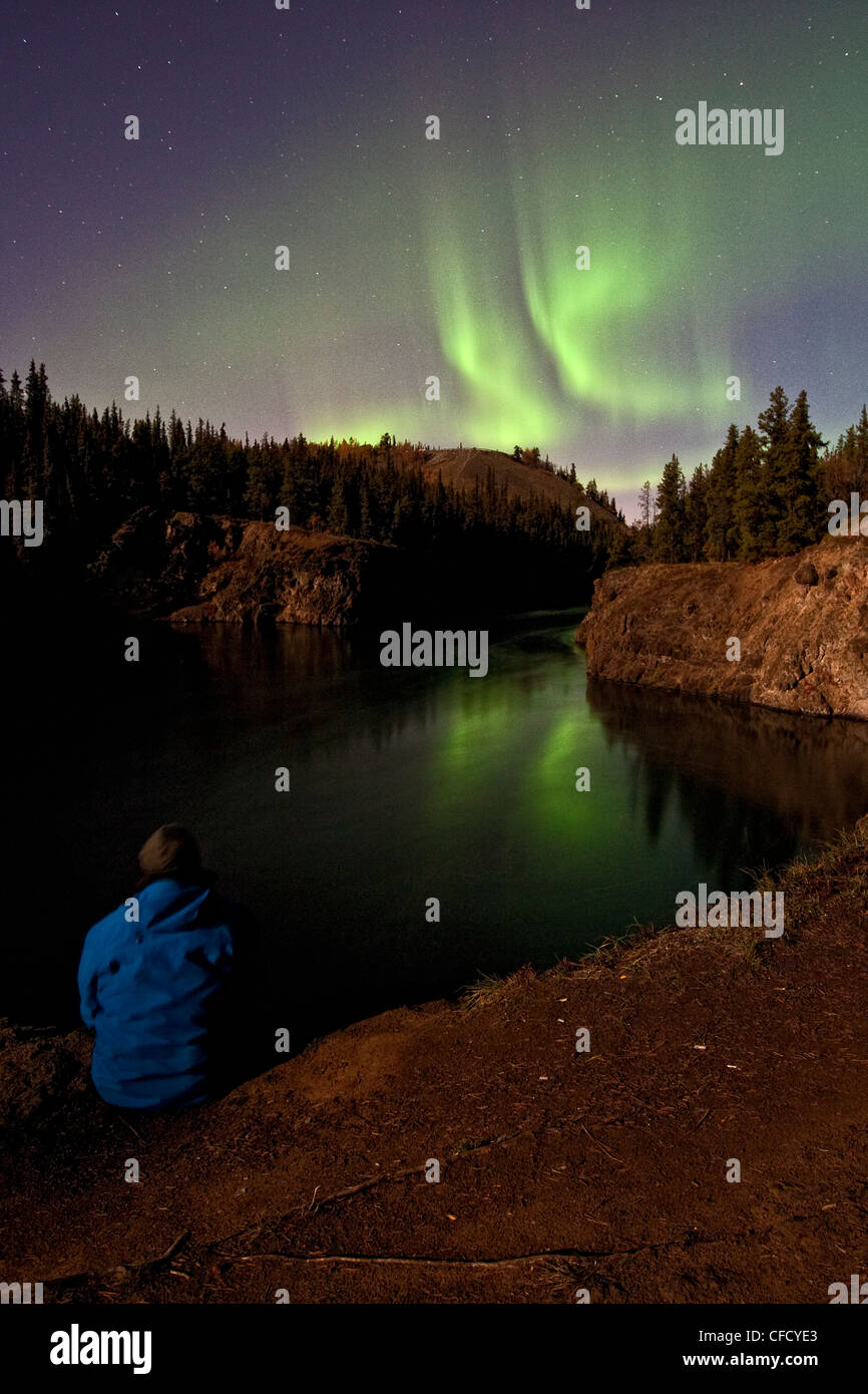 Person watching nothern lights over Miles Canyon, Whitehorse, Yukon, Canada. - Stock Image
