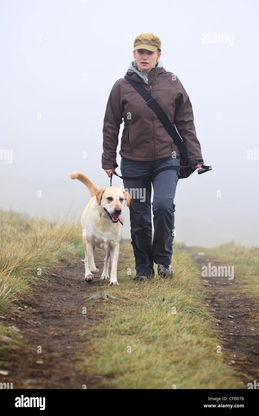 Woman walking her Yellow Labrador Retriever dog on a rainy, foggy day. Nose Hill Park, Calgary, Alberta, Canada. - Stock Image
