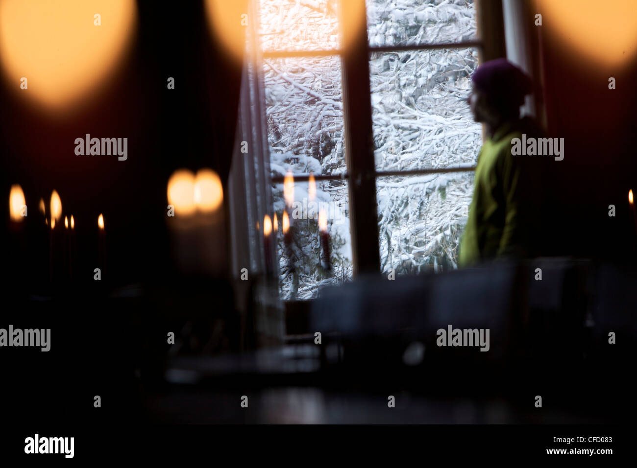 Mid adult man looking out a window of a hostel, Chandolin, Anniviers, Valais, Switzerland Stock Photo