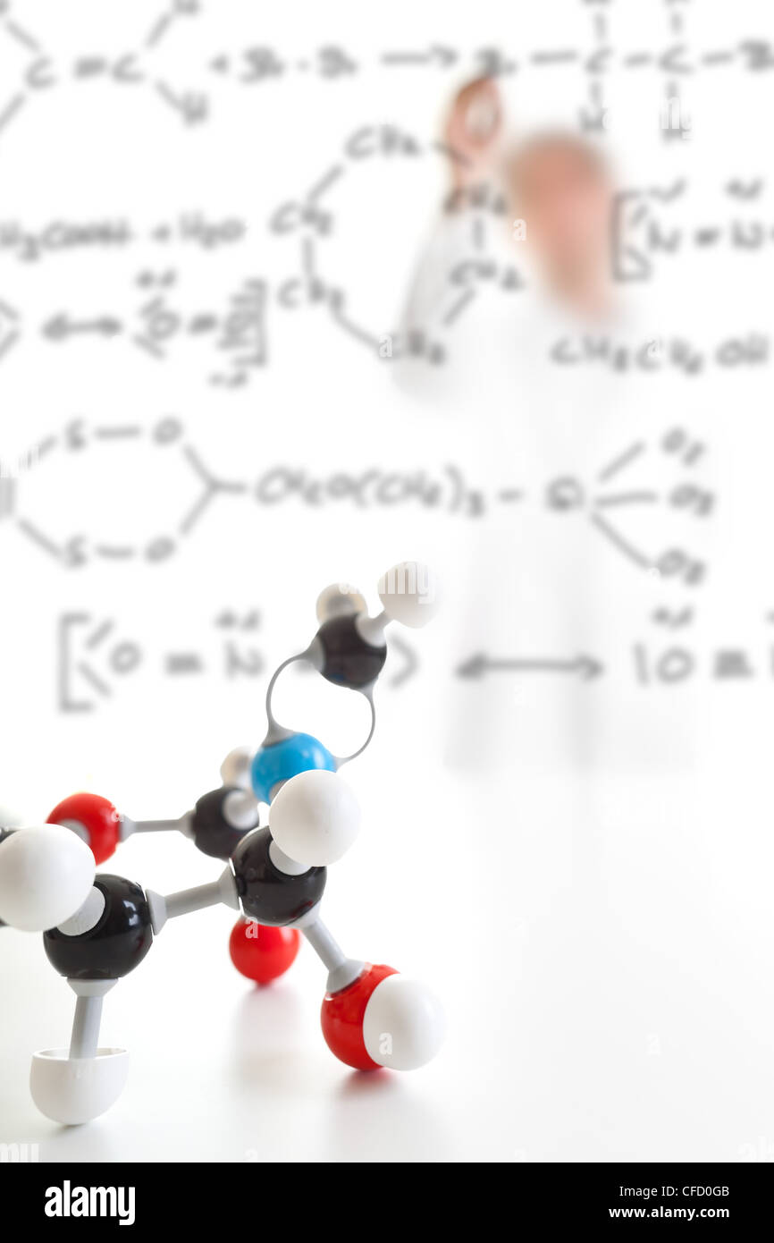 Molecule model with researcher taking notes in the background - Stock Image