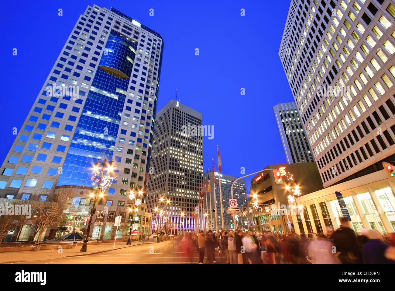 Skyline and crowd gathered on Portage Avenue at night. Winnipeg, Manitoba, Canada. - Stock Image