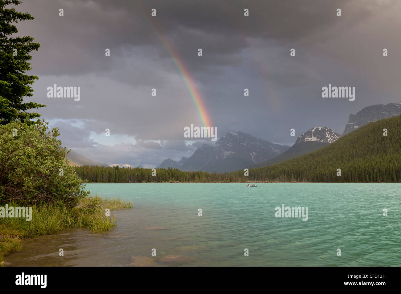 Boats and a canoe with rainbow over Lower Waterfowl Lake, Banff National Park, Alberta, Canada Stock Photo