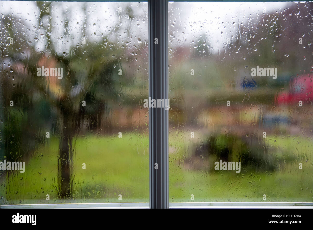 Rain drops on house window wet weather day looking out - Stock Image