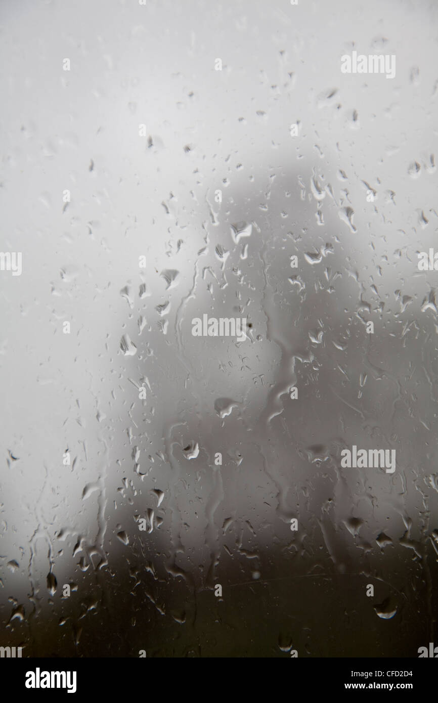 Raindrops on glass window pane looking out - Stock Image