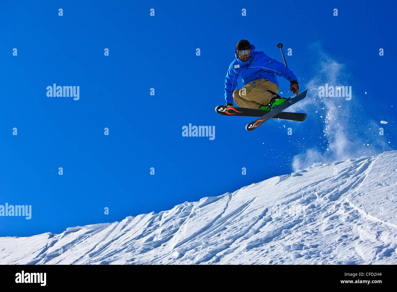 Skier jumping over a ridge on the upper slopes of Whistler Mountain, Whistler Blackcomb, Whistler, British Columbia, - Stock Image