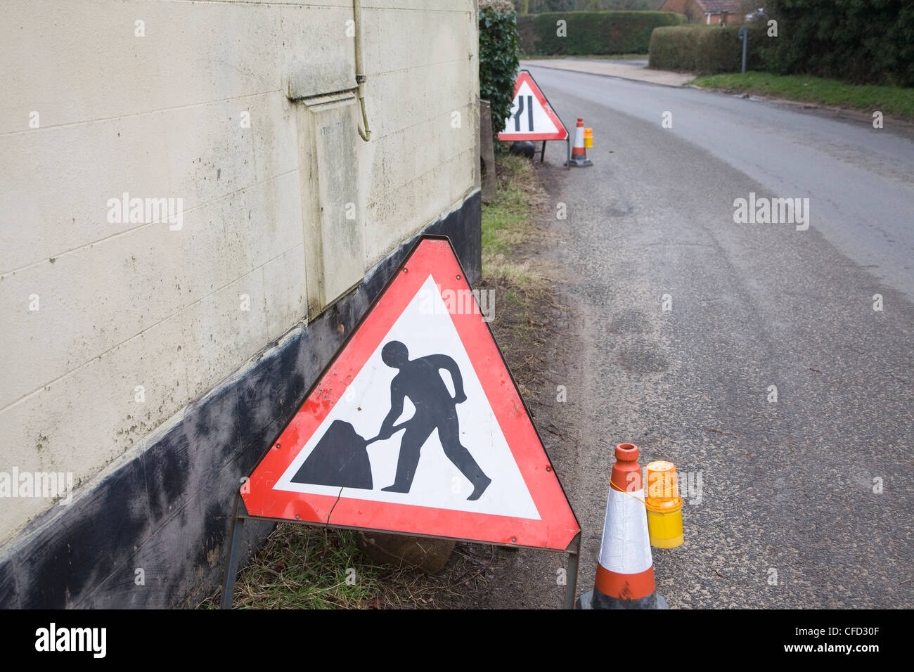 Man at work triangle road sign on street - Stock Image