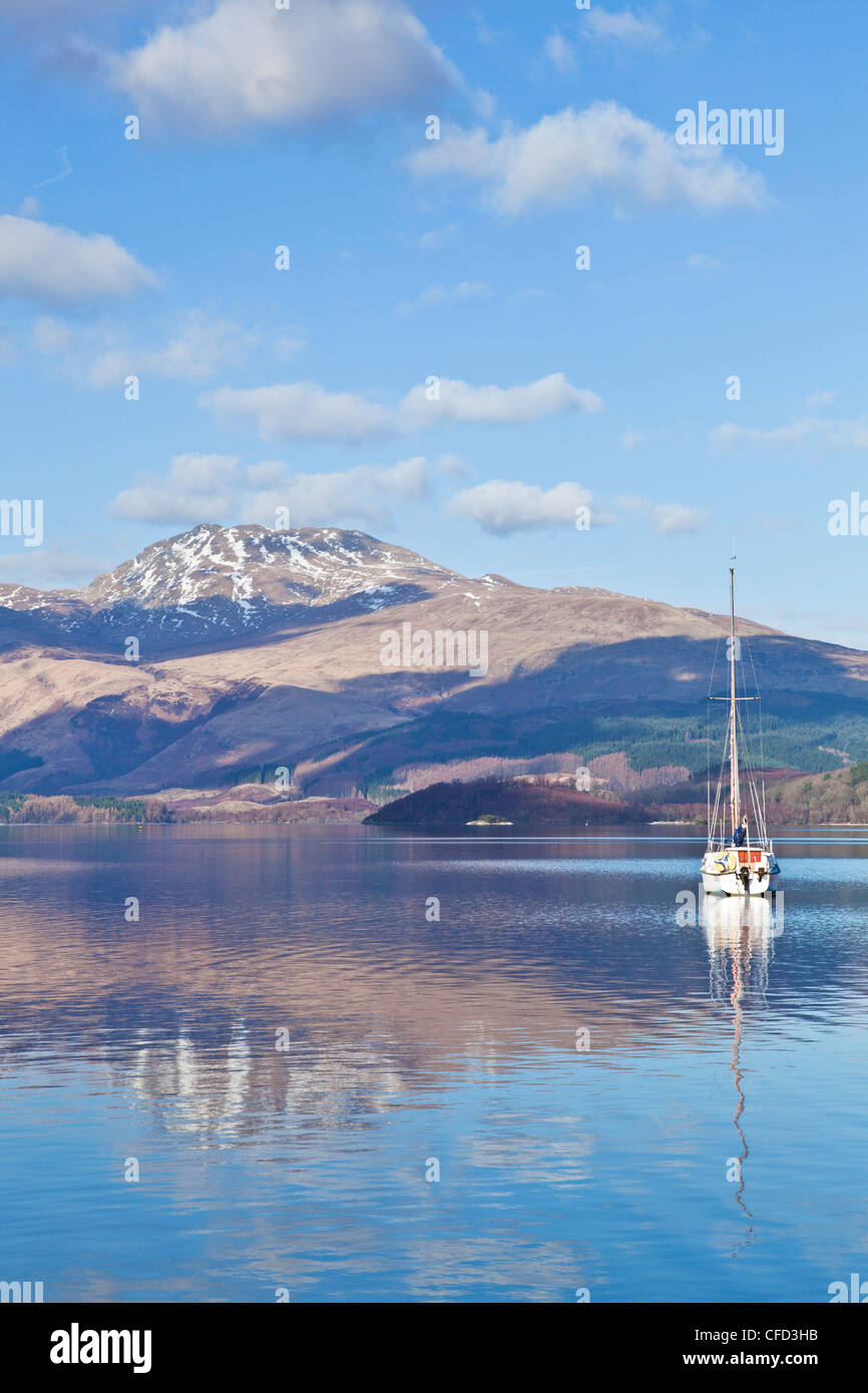 Loch Lomond with sailing boat, snow covered Beinn Uird behind, from Luss Jetty, Luss, Argyll and Bute, Scotland, - Stock Image