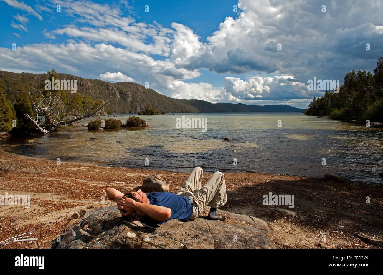 Trekker is relaxing at Lake Meston, Walls of Jerusalem National Park, UNESCO World Nature Site, Tasmania, Australia - Stock Image