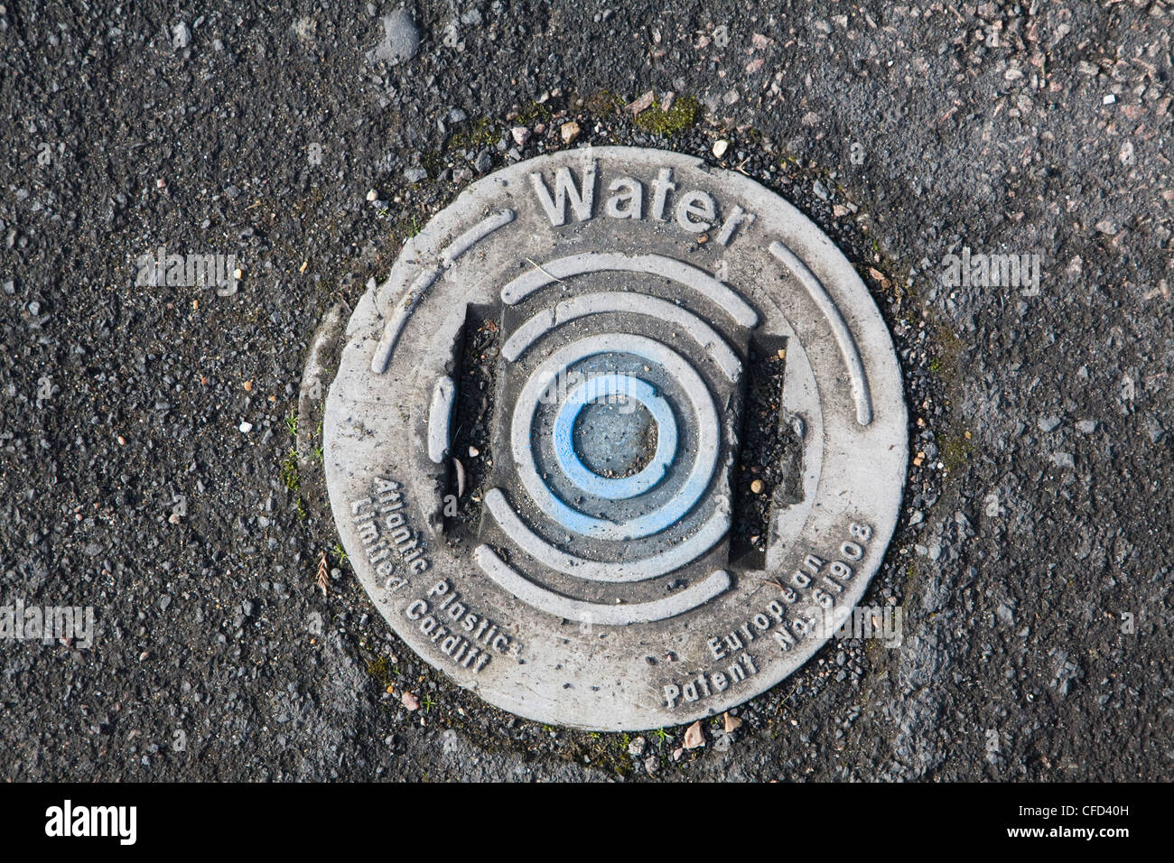 Water supply for household cover set in tarmac - Stock Image