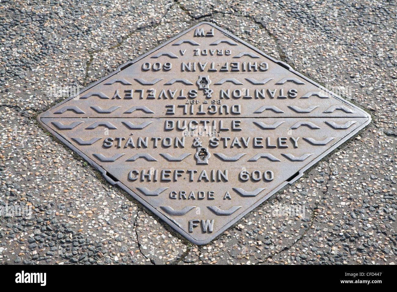 Iron manhole cover tarmac road - Stock Image