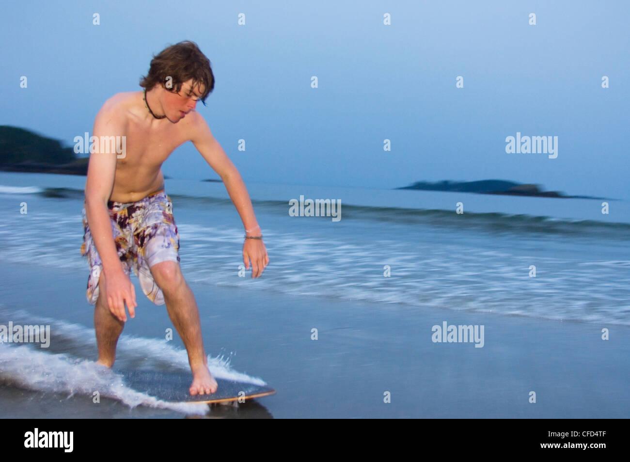 teenage boys skim board on wet sand, MacKenzie Beach at Tofino Stock ...