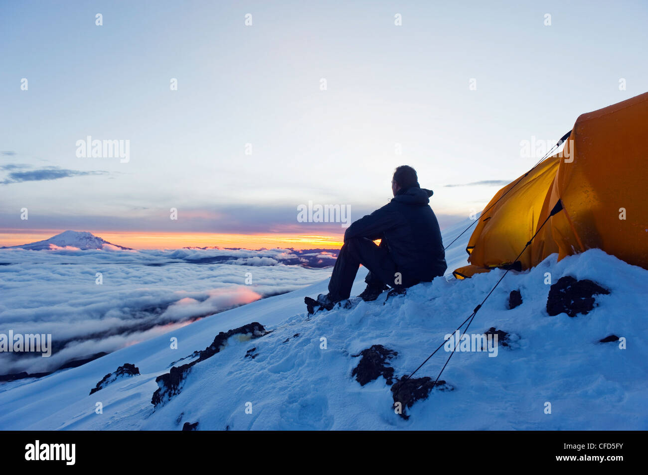 Climber looking at sunrise on Volcan Cotopaxi, 5897m, highest active volcano in the world, Ecuador, South America - Stock Image