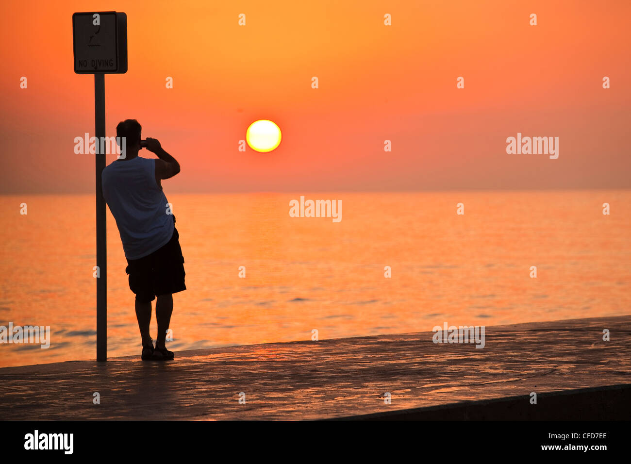 Man leaning on a sign post and photographing the sunrise, Key West, Florida, United States of America. - Stock Image