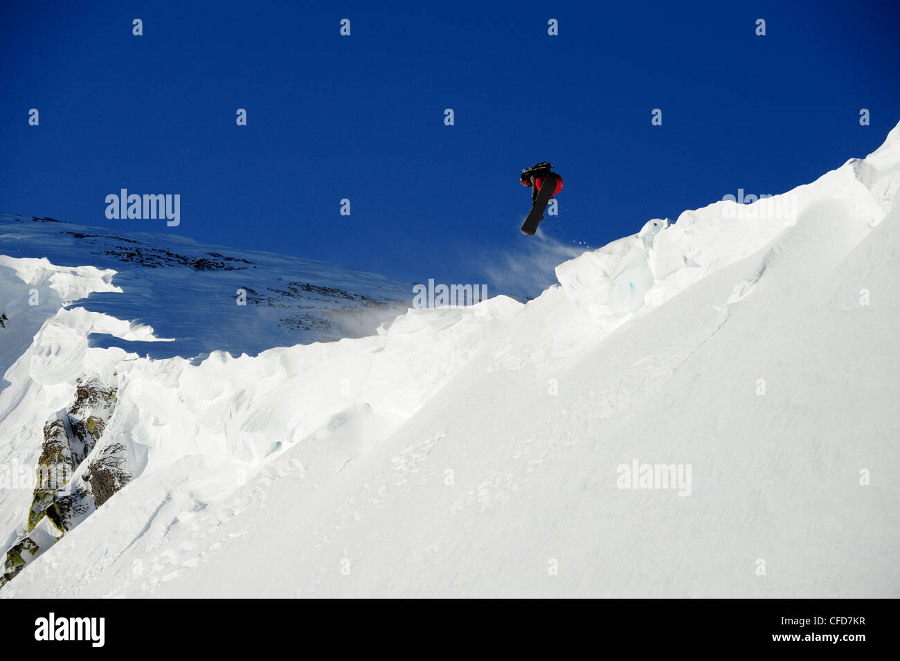A snowboarder catches air off a cornice in the Lake Tahoe backcountry, California. - Stock Image