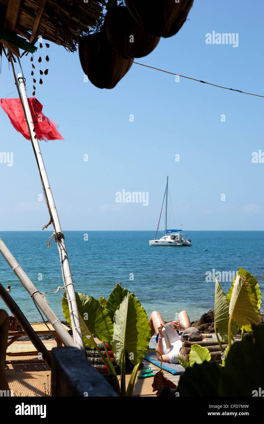 Resort with reading tourist and a sail boat, Koh Lanta, Andaman Sea, Thailand - Stock Image