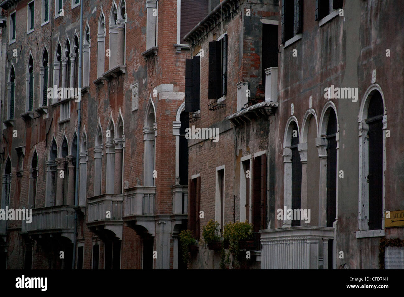 Row of Venetian buildings with arched and shuttered windows, Venice Italy - Stock Image