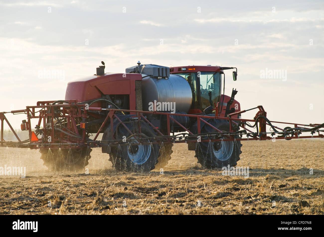 A high clearance sprayer applies liquid fertilizer on a newly seeded field, near Dugald, Manitoba, Canada - Stock Image