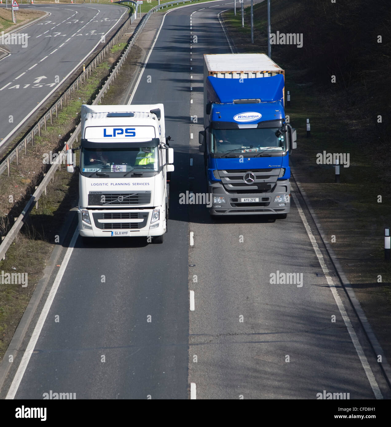 Two HGV lorries one over-taking the other on dual carriageway - Stock Image
