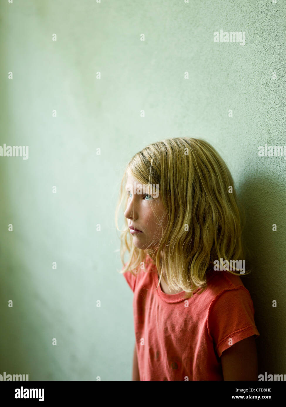 a girl poses leans against the wall looking up to the ceiling - Stock Image