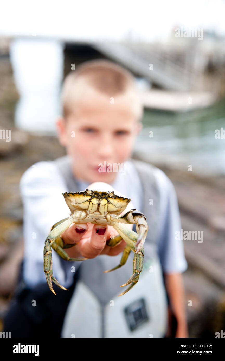 a boy holds his catch up for a photo - Stock Image