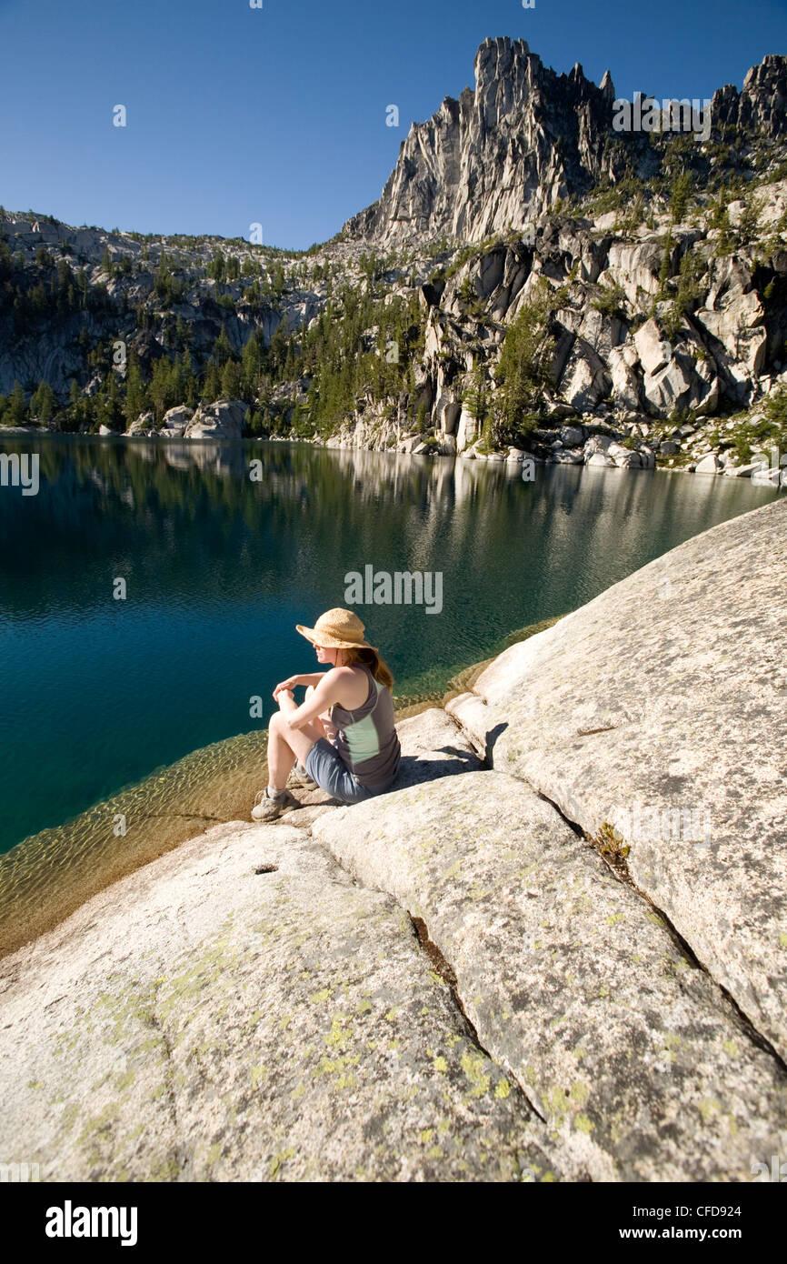 Woman sitting on the shore of Lake Viviane, Enchantment lakes, Alpine Lakes Wilderness, Levenworth, Washington State, - Stock Image