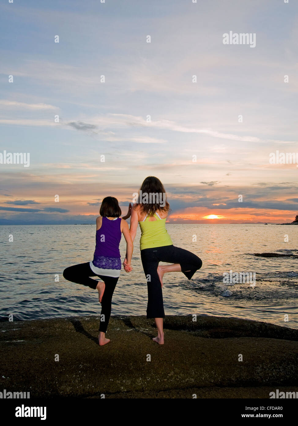 mother daughter spend beautiful sunset practicing - Stock Image