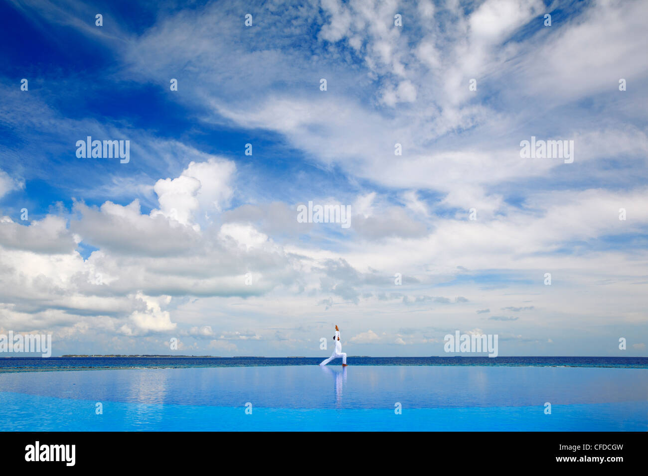 Young man meditating by infinity pool, Maldives, Indian Ocean, Asia - Stock Image