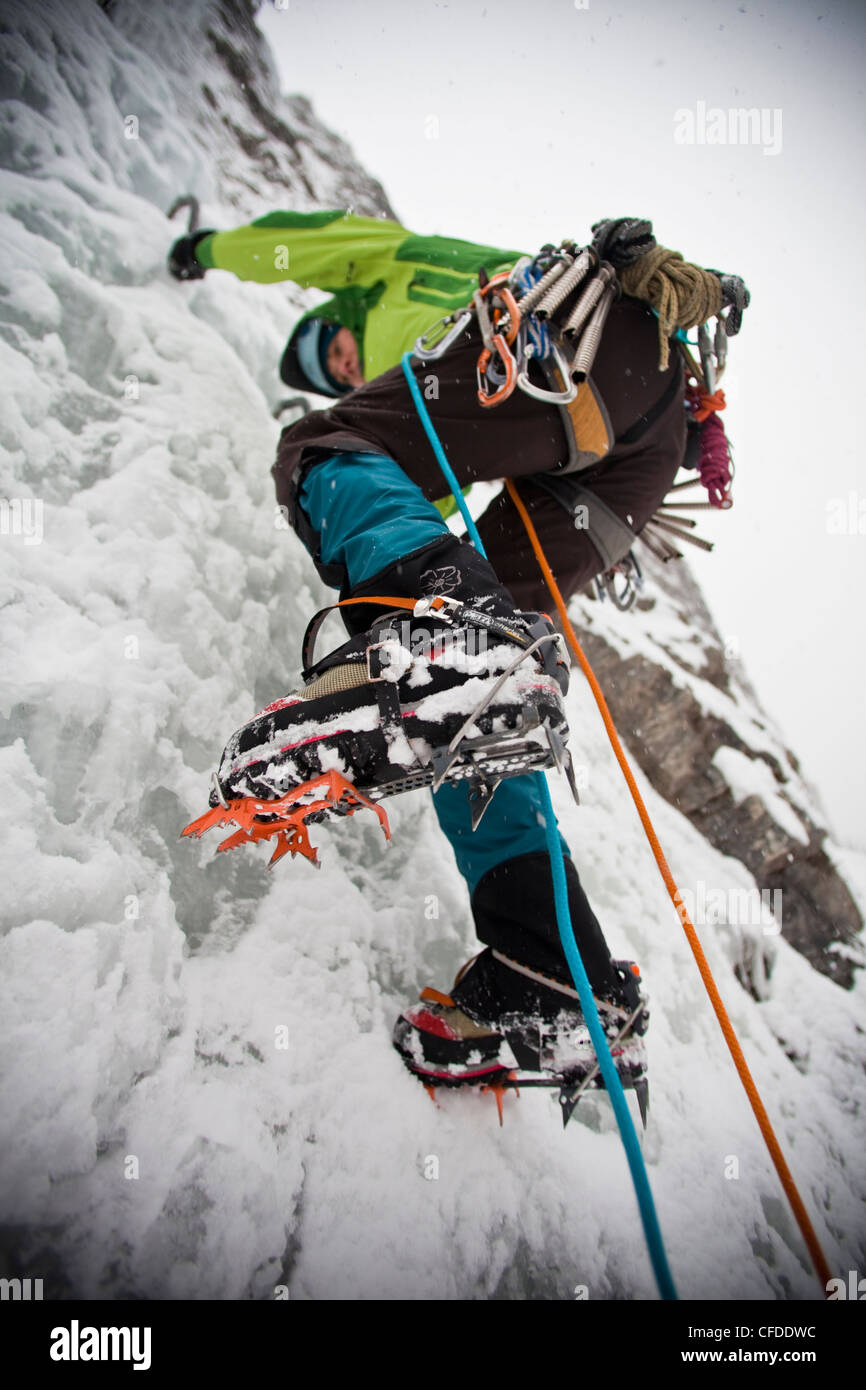 female ice climber setting crampons she climbs - Stock Image