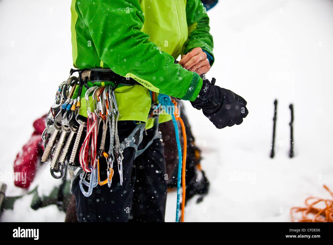 A woman gets ready to ice climb Moonlight WI4, Even Thomas Creek, Kananaskis, Alberta, Canada - Stock Image