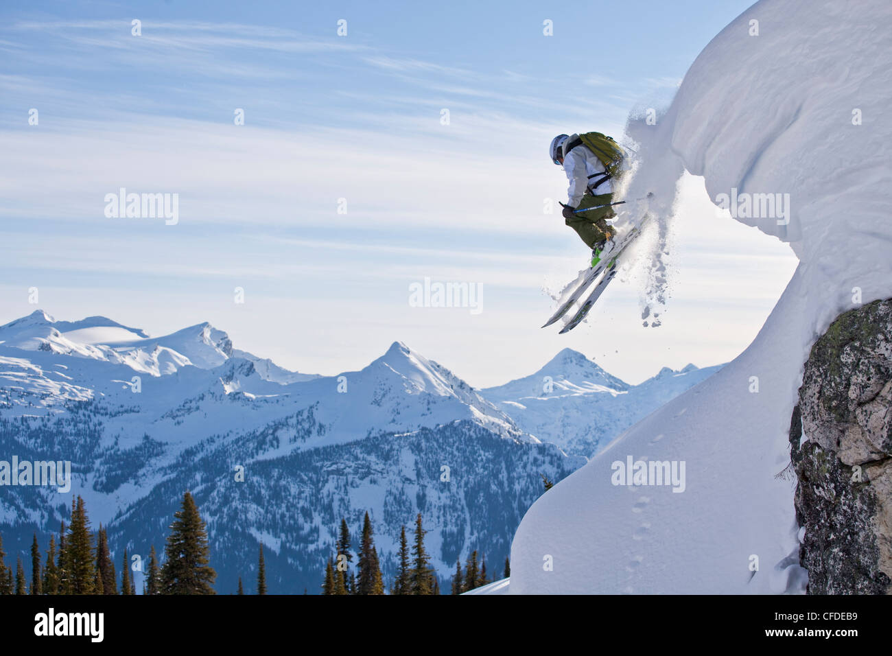 A male skier airs off a snow pillow while on a cat ski trip. Monashee Mountains, Britsh Columbia, Canada - Stock Image
