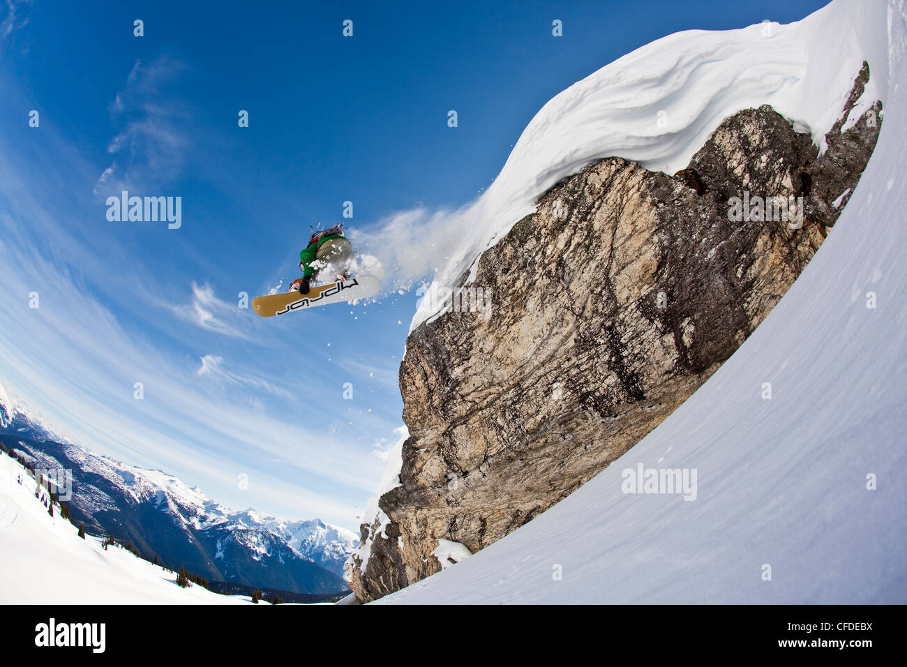 A snowboarder airs off a snow pillow while on a cat ski trip. Monashee Mountains, Vernon, Britsh Columbia, Canada - Stock Image