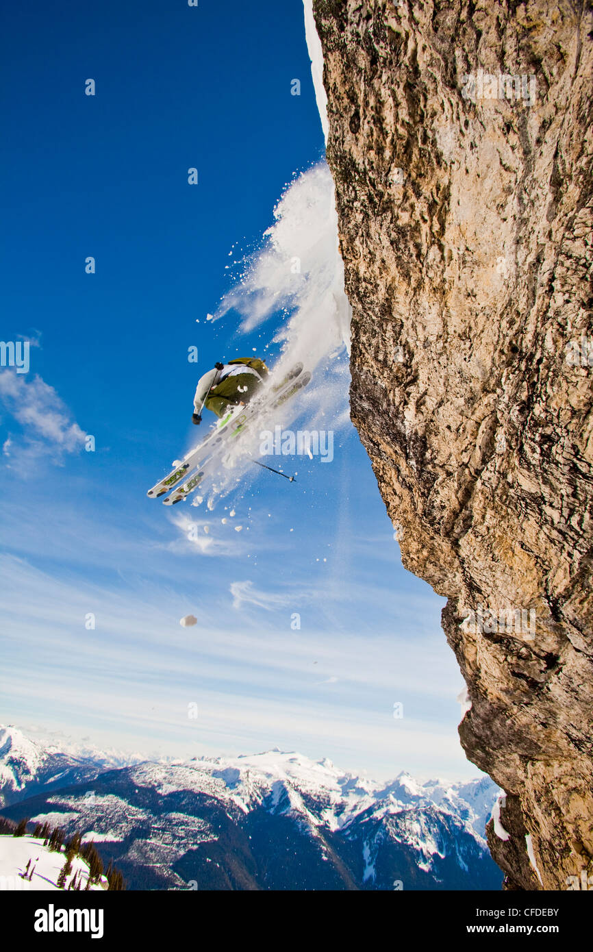A male skier airs a cliff while on a cat ski trip, Monashees, Vernon, Britsh Columbia, Canada - Stock Image