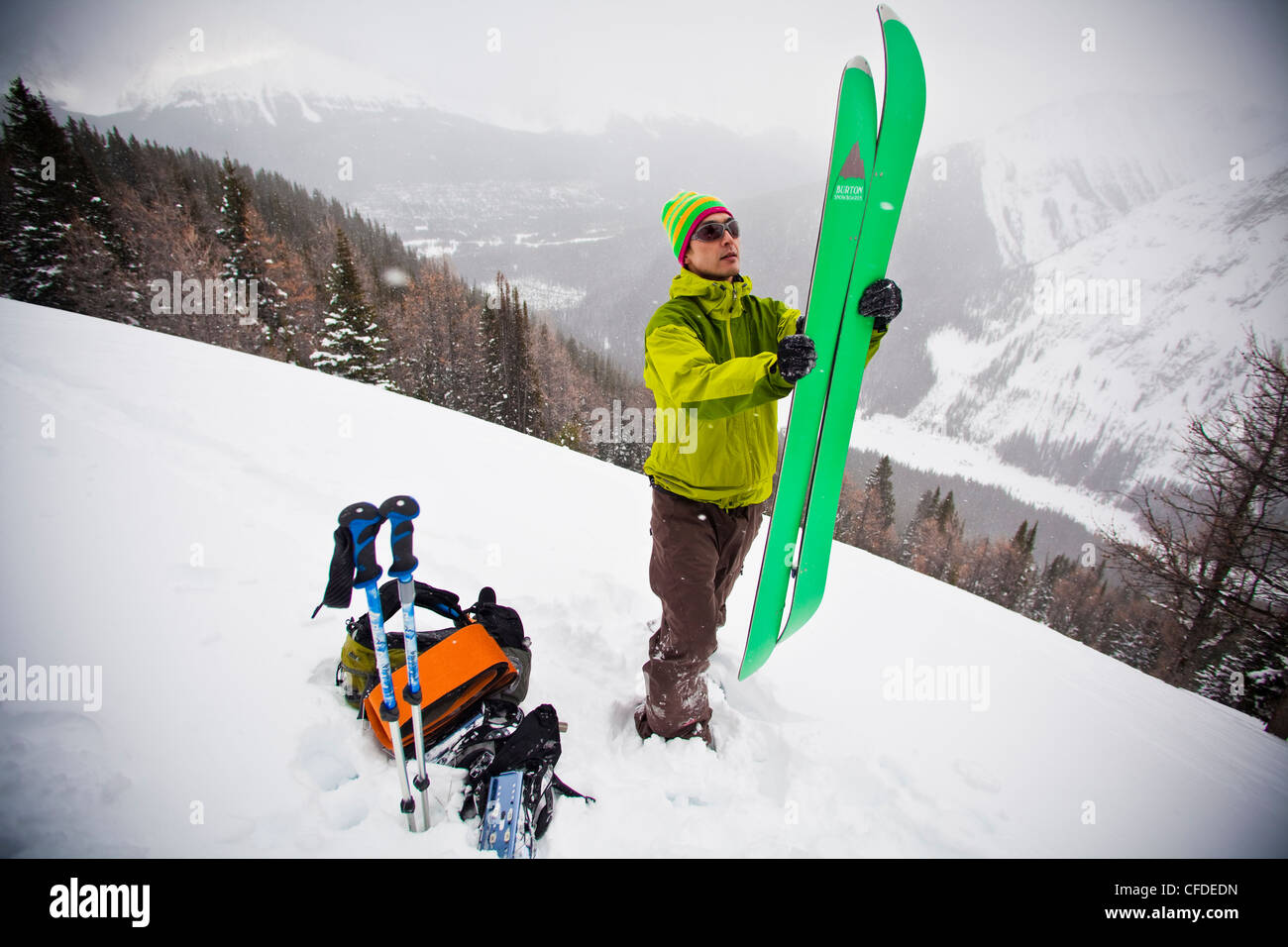 A backcountry snowboarder puts together his splitboard for the ride down, Tryst Lake, Kananaskis, Alberta, Canada - Stock Image