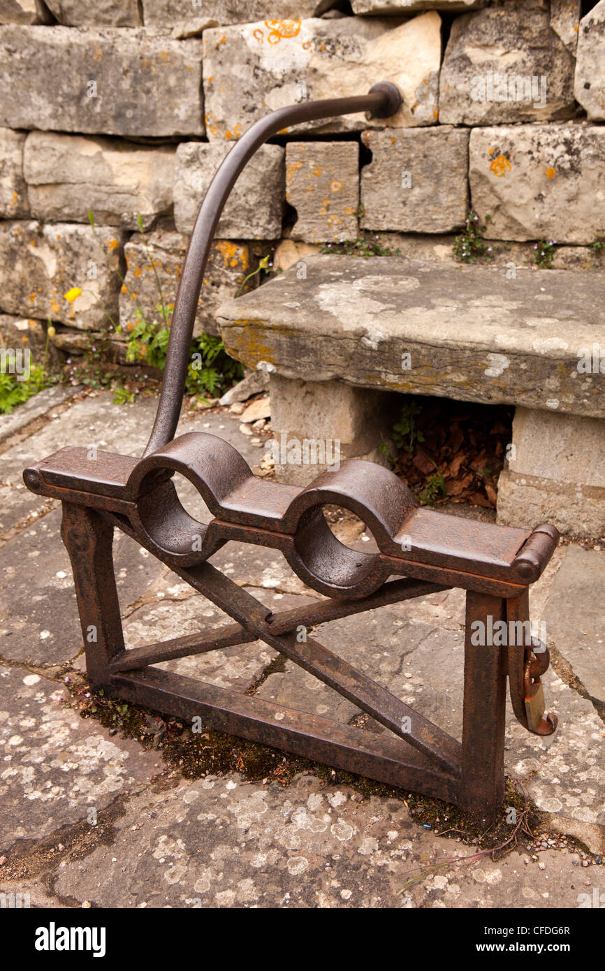 UK, Gloucestershire, Stroud, Painswick, historic iron spectacle stocks at edge of churchyard - Stock Image