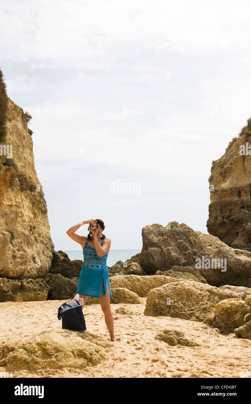 Woman in swimwear on a beach taking a picture, Albufeira, Algarve region, Portugal, Europe. This image is model - Stock Image