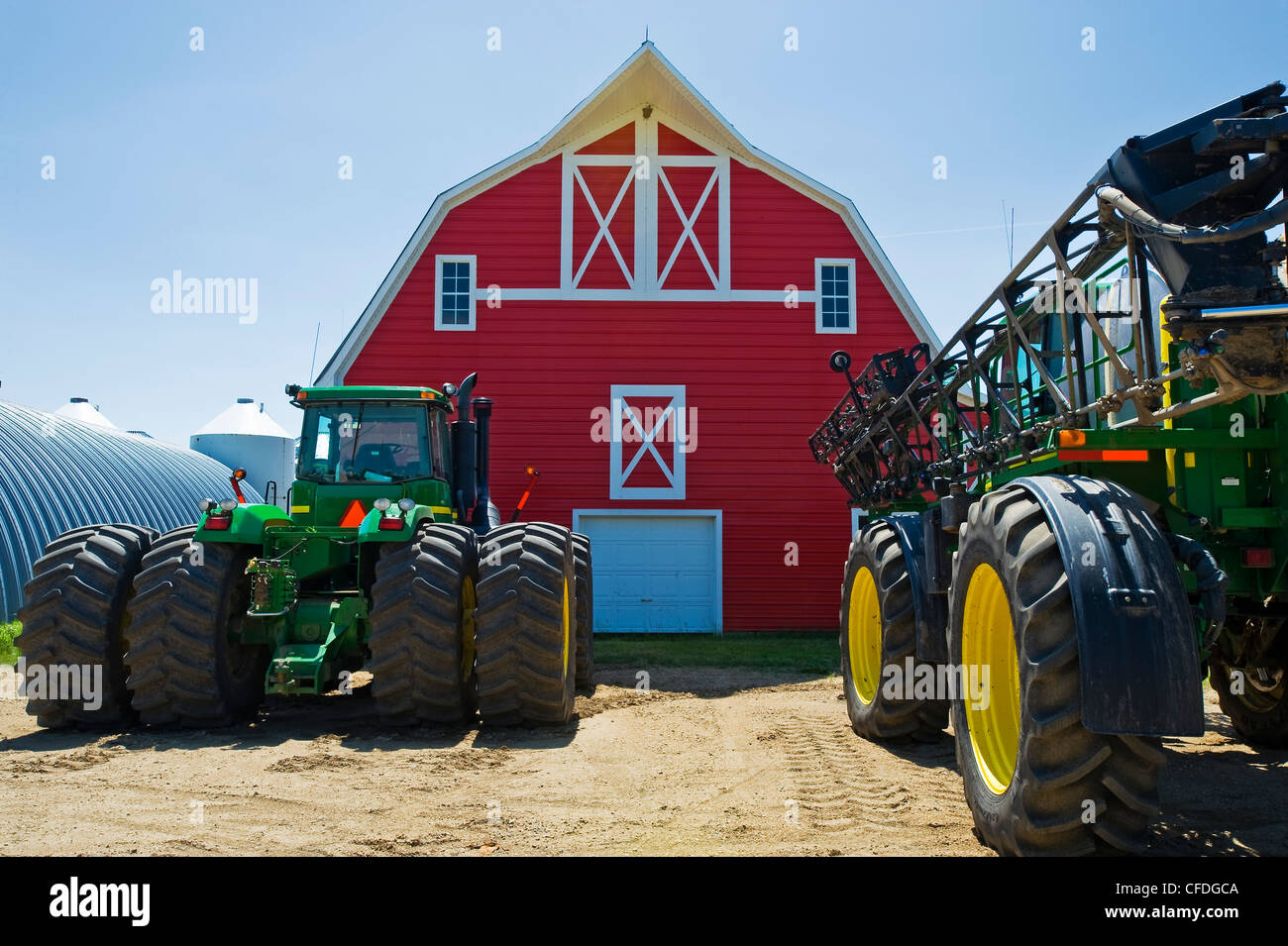 closeup of tractor and sprayer with red barn in the background near Torquay, Saskatchewan, Canada - Stock Image