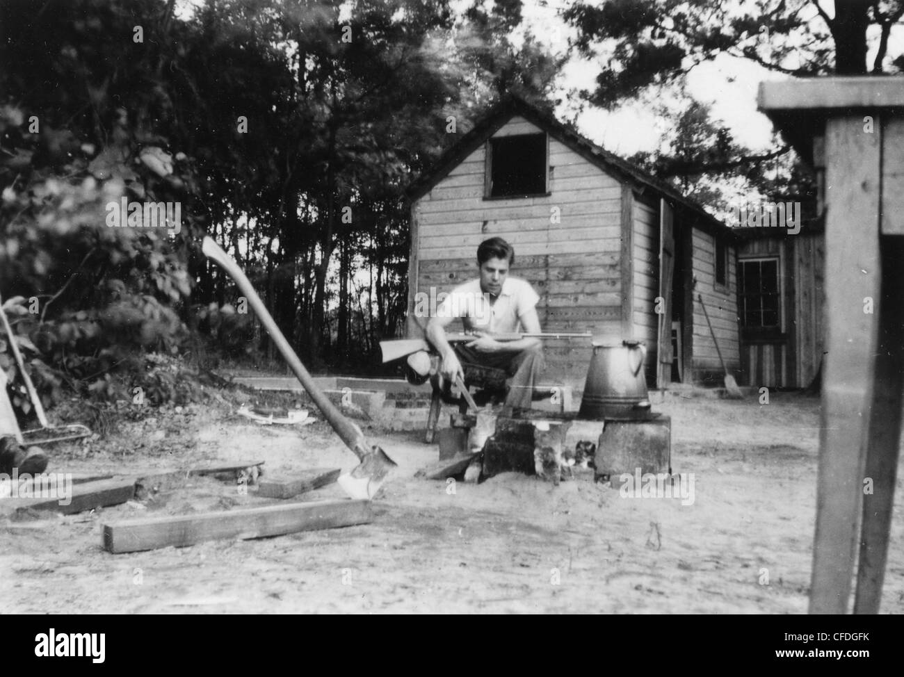 young man with rifle outside homestead house navy uniform fire kettle 1920s 1930s dreamlike - Stock Image
