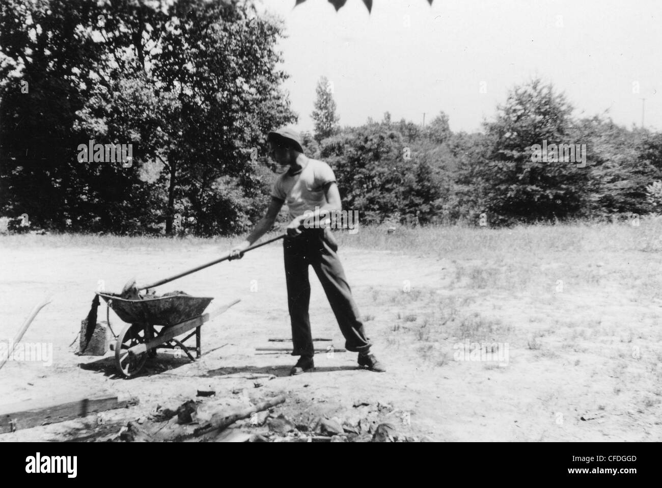 boy putting rocks in vintage wheel barrow during the 1940s 1930s midwest America manual labor teenage boy man - Stock Image