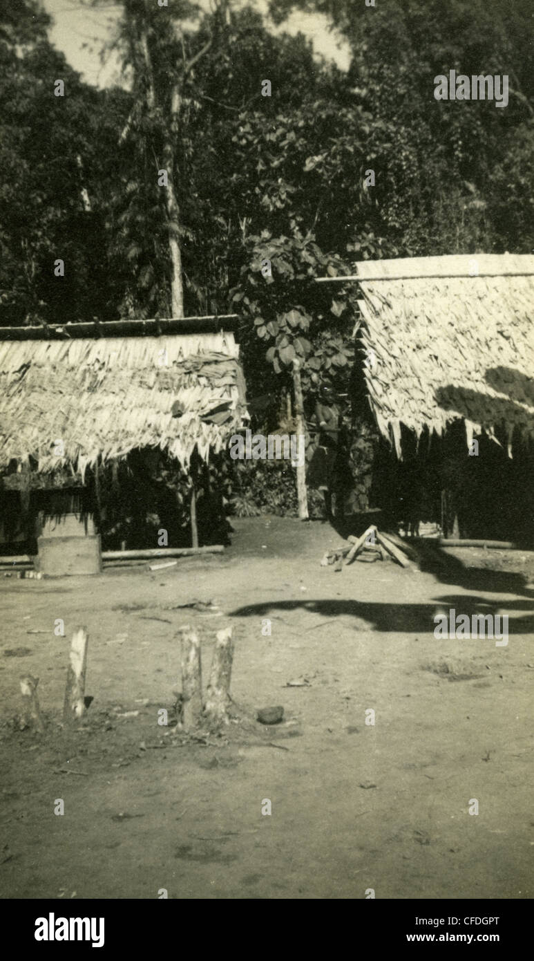 Thatched roof huts in village on South Pacific Island during WWII native housing architecture - Stock Image