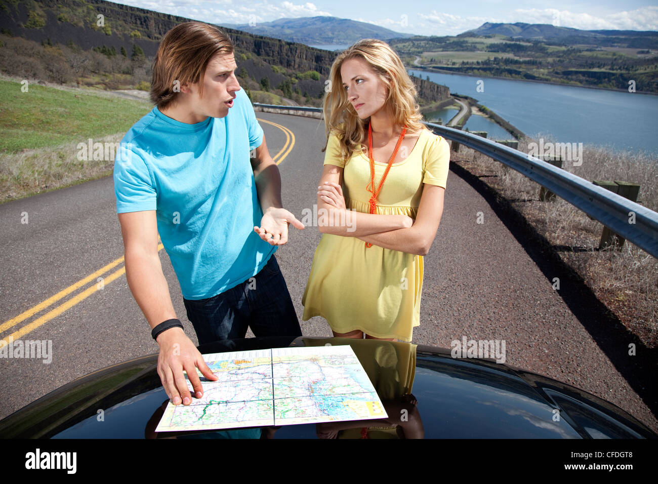 A couple argues while reading a road map on their car hood. - Stock Image