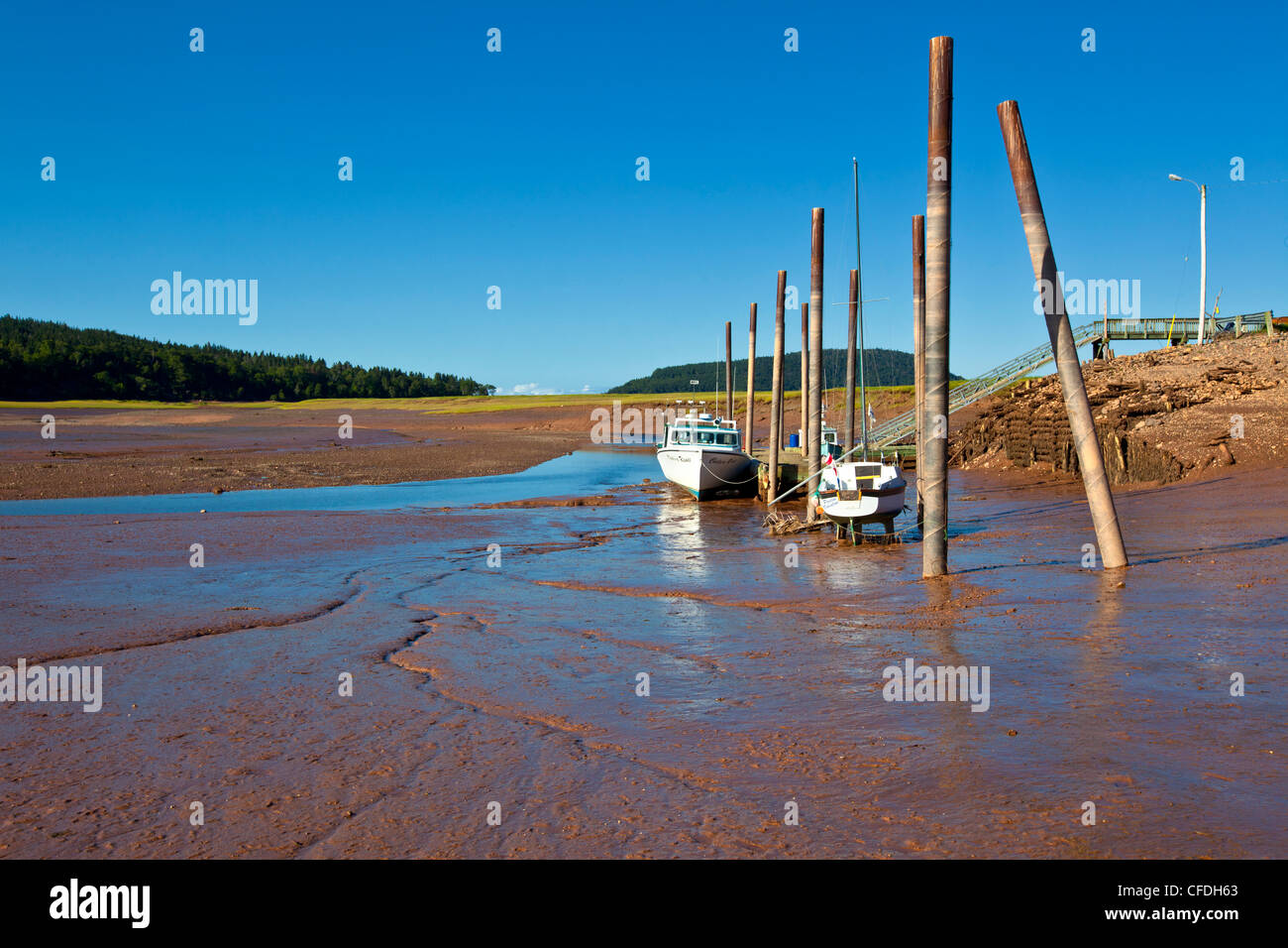 Fishing boats tied up at wharf at low tide, Five Islands, Nova Scotia, Canada - Stock Image