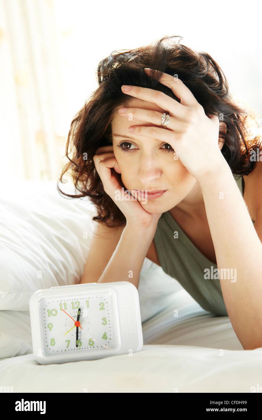 Woman looking at clock - Stock Image