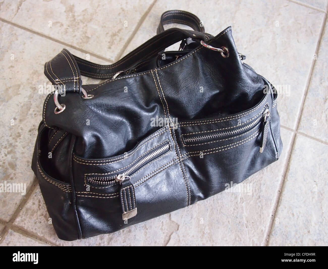 Black leather purse in tile floor - Stock Image