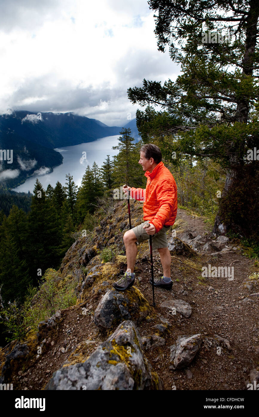 A man in an orange jacket stads on a high cliff while over looking a beautiful lake and green hills. - Stock Image