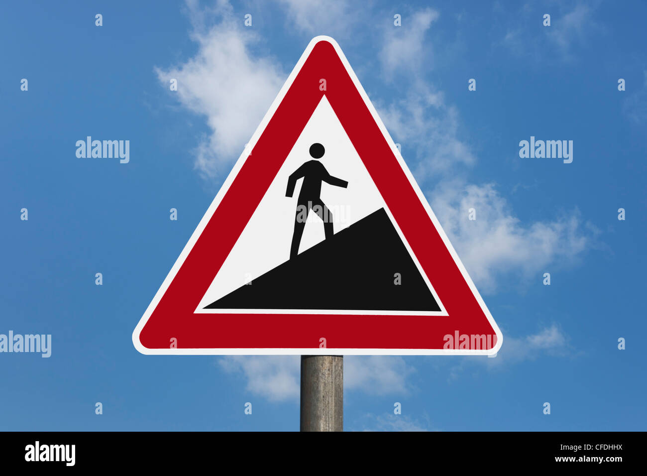 Detail photo of a danger sign 'Upward gradient', a man goes up, background sky. - Stock Image
