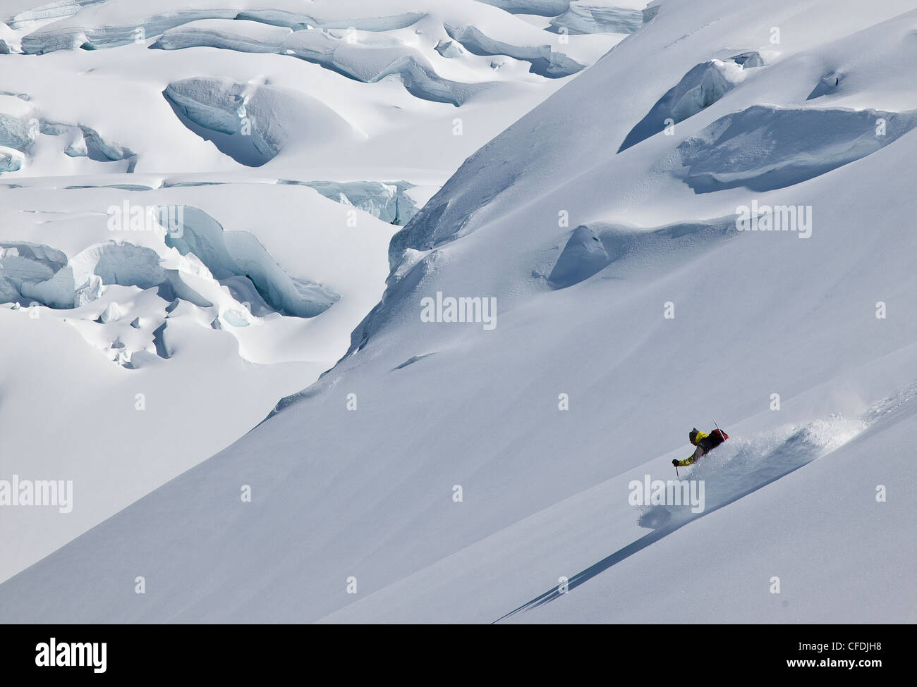 Backcountry skier skiing fresh powder in the Selkirk Range near the Fairy Meadows backcountry hut, British Columbia, - Stock Image