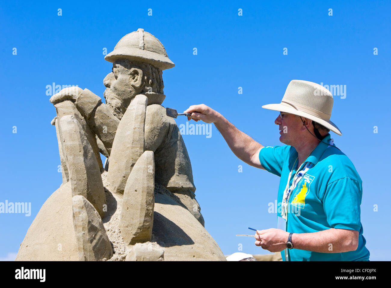 sand castle competitor applies finishing touches - Stock Image
