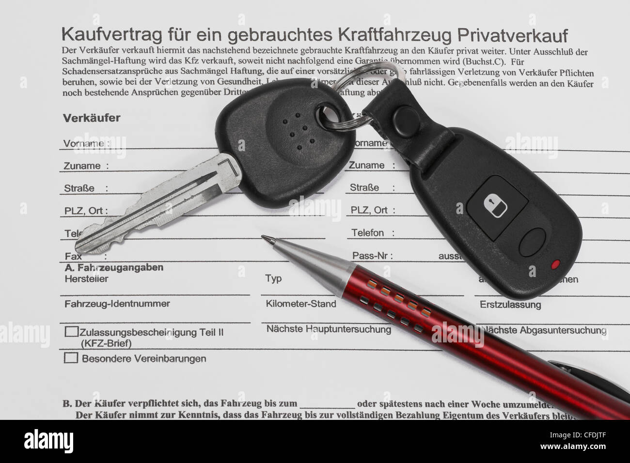 Detail photo of a car sales agreement in German, alongside are car key and a pen Stock Photo