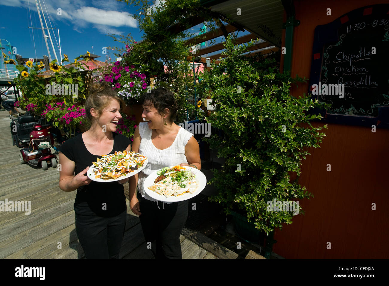 Two servers share laugh Penny's Palappopular - Stock Image